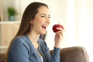 Woman smiling, eating an apple