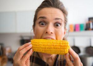 happy woman bites a corn cob